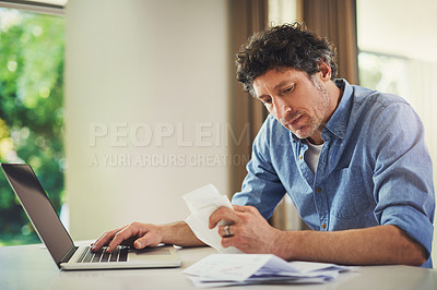 Buy stock photo Shot of a mature man going over his finances at home