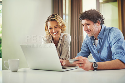 Buy stock photo Shot of a mature couple using a laptop and credit card together at home
