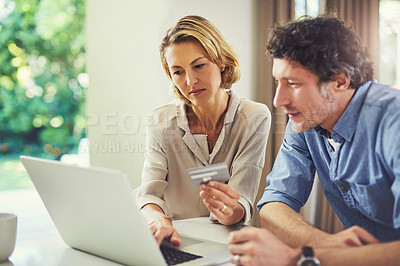 Buy stock photo Shot of a mature couple using a credit card while going over their finances at home