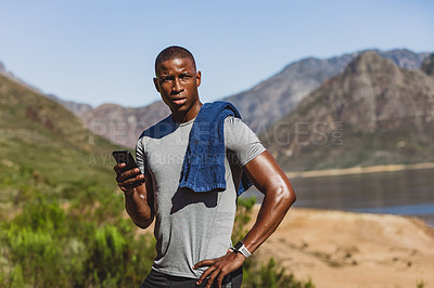 Buy stock photo Shot of a sporty young man using his cellphone while out for a run in nature
