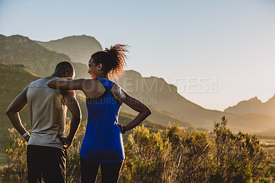 Buy stock photo Rearview shot of a sporty young couple taking a break from their workou