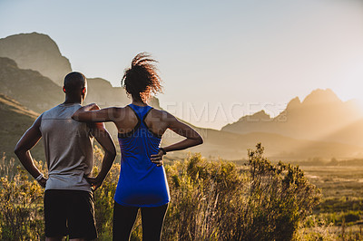 Buy stock photo Shot of a sporty young couple looking at the view while out in nature