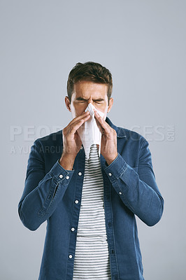 Buy stock photo Cropped shot of a man blowing his nose against a grey background