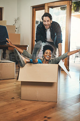 Buy stock photo Full length shot of an affectionate young couple being playful with boxes while moving into their new home