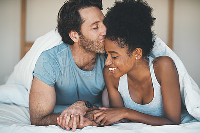 Buy stock photo Shot of an affectionate middle aged man kissing his wife on her forehead while relaxing on their bed at home