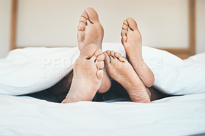 Buy stock photo Cropped shot of an unrecognizable young couple's feet lying on their bed at home