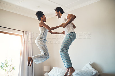 Buy stock photo Full length shot of an affectionate young couple jumping on their bed at home