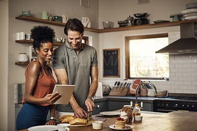 Buy stock photo Cropped shot of an affectionate young couple using a digital tablet while preparing breakfast in their kitchen at home