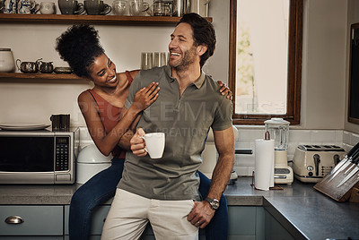 Buy stock photo Cropped shot of an affectionate young couple laughing together while spending quality time in their kitchen at home