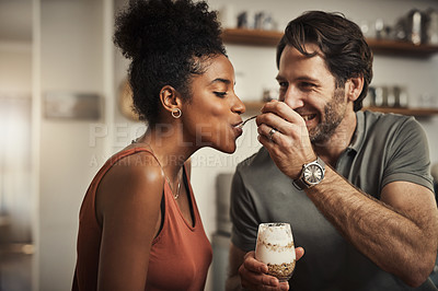 Buy stock photo Cropped shot of an affectionate middle aged man feeding his wife dessert in their kitchen at home