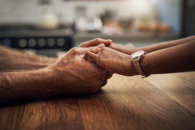 Buy stock photo Cropped shot of an unrecognizable young couple holding hands together compassionately while sitting on a table at home