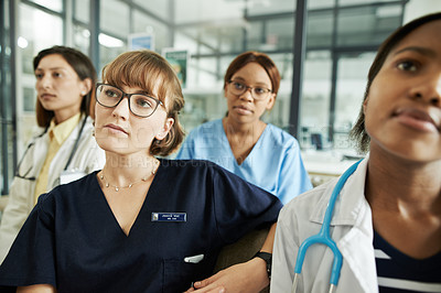 Buy stock photo Shot of a group of young doctors attending a conference in a modern hospital