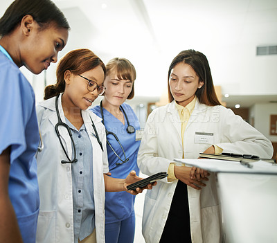 Buy stock photo Shot of a team of young doctors using a smartphone while having a discussion in a modern hospital