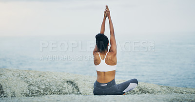 Buy stock photo Rearview shot of an unrecognizable woman sitting cross legged and doing yoga alone by the ocean during an overcast day