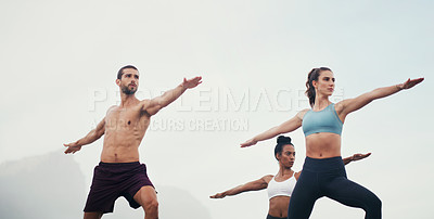 Buy stock photo Cropped shot of three young people standing in a warrior position while doing yoga on the beach