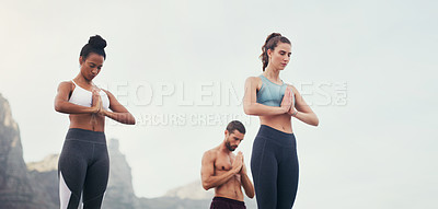 Buy stock photo Cropped shot of a group of young people standing and meditating together while on the beach during an overcast day