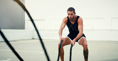 Buy stock photo Cropped shot of a handsome young sportsman working out with battle ropes outdoors during the day