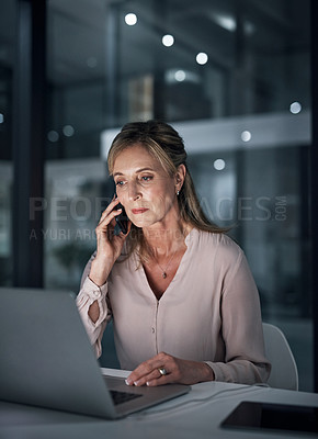 Buy stock photo Shot of a mature businesswoman talking on a cellphone while using a laptop in an office at night