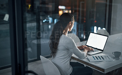 Buy stock photo Rearview shot of a young businesswoman using a laptop in an office at night