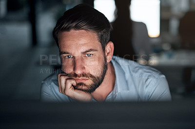 Buy stock photo Shot of a young businessman looking bored while working on a computer in an office at night