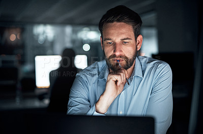 Buy stock photo Shot of a young businessman biting a pen while working on a laptop in an office at night