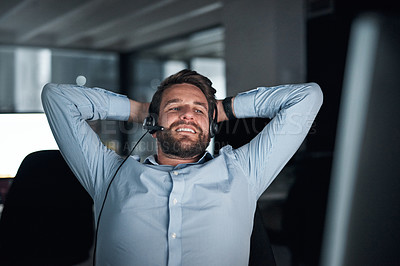 Buy stock photo Shot of a young call centre agent taking a break while working in an office at night