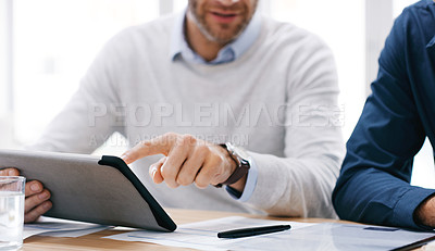 Buy stock photo Closeup shot of two unrecognisable businessmen using a digital tablet together in an office