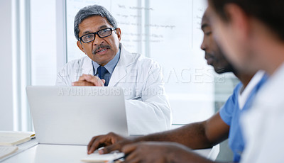 Buy stock photo Shot of a group of medical practitioners using a laptop during a meeting in a hospital boardroom