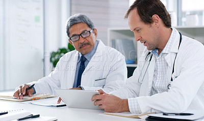 Buy stock photo Shot of two doctors working on a digital tablet together
