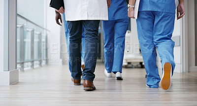 Buy stock photo Closeup shot of a group of unrecognisable doctors walking in a hospital