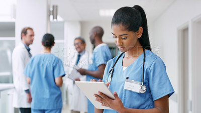 Buy stock photo Shot of a young nurse using a digital tablet in a hospital corridor