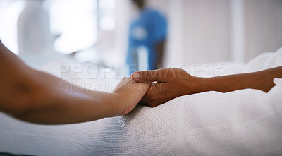 Buy stock photo Closeup shot of an unrecognisable woman holding a patients hand in comfort in a hospital ward