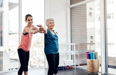 Buy stock photo Shot of a fitness instructor helping a senior woman during a yoga class