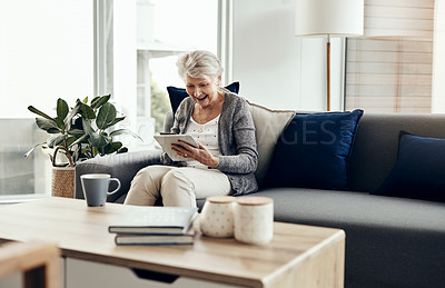 Buy stock photo Shot of a senior woman holding her credit card while browsing on a digital tablet