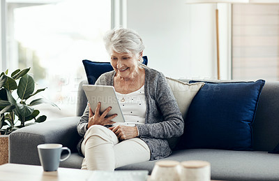 Buy stock photo Shot of a senior woman using a digital tablet while relaxing at home