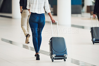 Buy stock photo Rearview shot of an unrecognizable businesswoman pulling a suitcase while walking through an airport terminal during the day