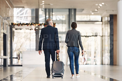 Buy stock photo Full length shot of two unrecognizable businesspeople walking through an airport terminal together during the day