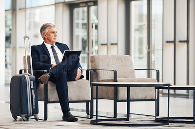 Buy stock photo Full length shot of a handsome mature businessman sitting and holding a folder of paperwork while in the office