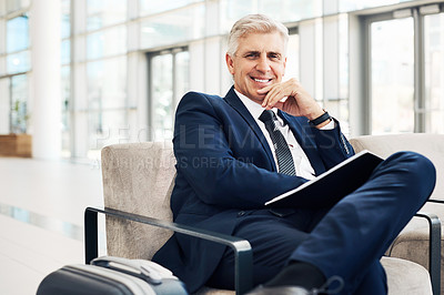 Buy stock photo Cropped portrait of a handsome mature businessman with his hand on his chin while sitting in an airport terminal