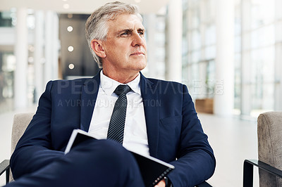 Buy stock photo Cropped shot of a handsome mature businessman sitting and looking away while contemplating in the office during the day
