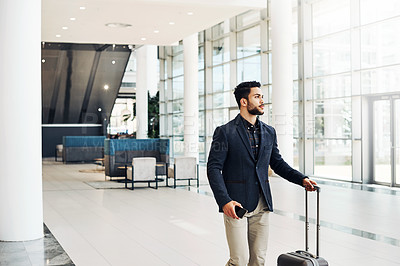 Buy stock photo Cropped shot of a handsome young businessman pulling a suitcase while walking through an airport terminal during the day