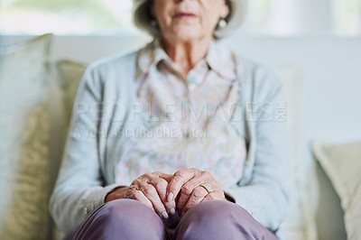 Buy stock photo Cropped shot of a senior woman sitting on the sofa alone while in the living room of a nursing home