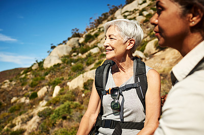 Buy stock photo Shot of two attractive senior women hiking together in the mountains