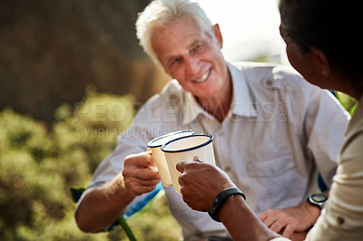 Buy stock photo Shot of a cheerful senior man sharing a toast with his wife while exploring out in the mountains