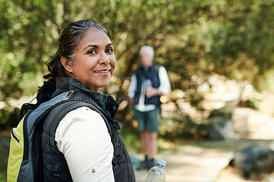 Buy stock photo Shot of a cheerful senior woman hiking with her husband out in the mountains