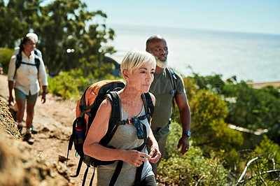Buy stock photo Shot of a group of senior people hiking together out in the mountains