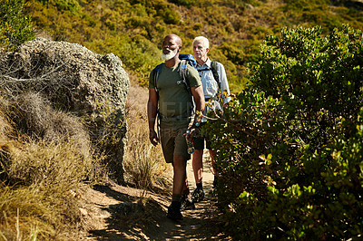 Buy stock photo Full length shot of two senior man hiking together out in the mountains