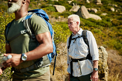 Buy stock photo Shot of two senior man hiking together out in the mountains