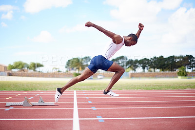 Buy stock photo Full length shot of a male sprinter running on the track
