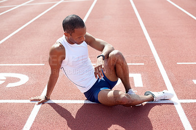 Buy stock photo Full length shot of a male sprinter checking his time while practicing on the track